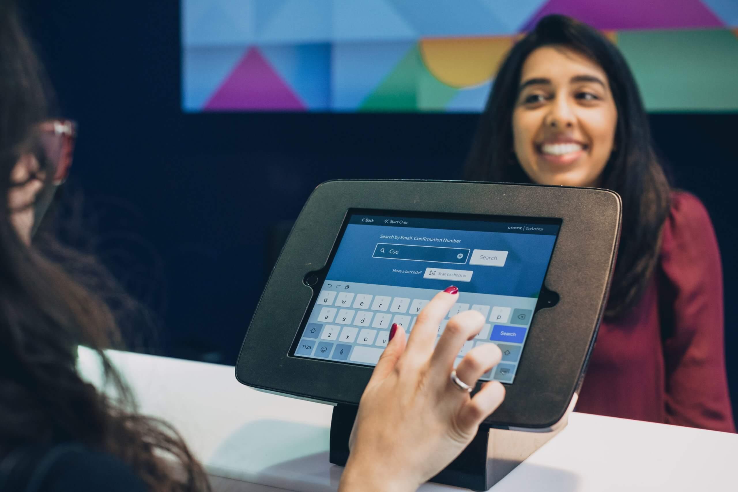 Frau verwendet Touchpad zum Einchecken auf einer Veranstaltung